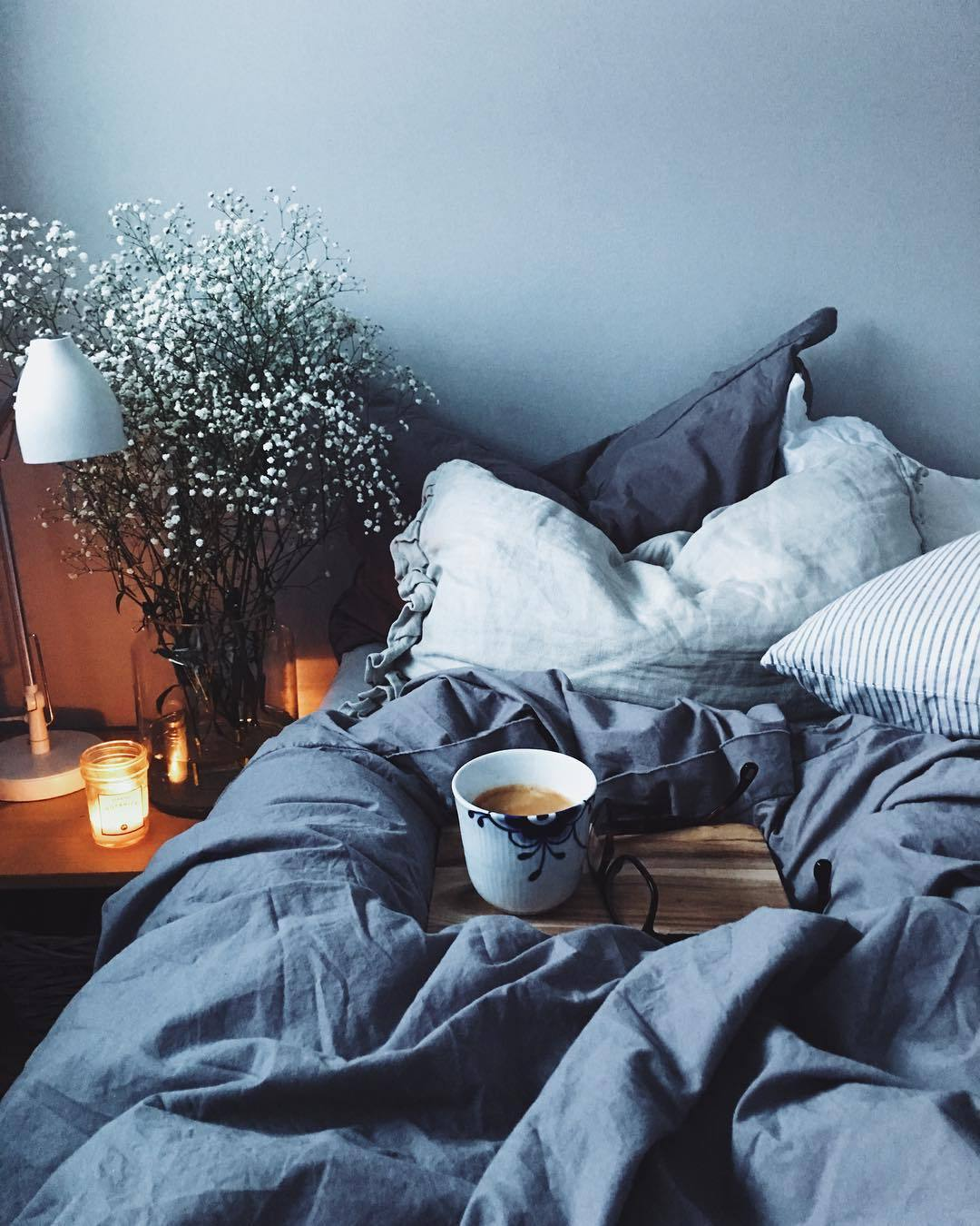 cosy winter bed with cup of tea. Blue bedsheets
