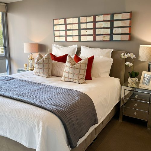 style a luxury bedroom with burnt orange cushions and mirror bedside tables